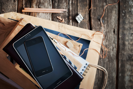 pedant: Stack of Accessories and Digital Gadgets for Business Men on Home Wooden Table. Tablet pc, phone, paper, different stuff. Top view