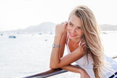 vida natural: La mujer feliz en un muelle en la mañana antes del fondo del mar azul y las montañas. Día de verano