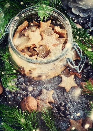 galletas de jengibre: Navidad galletas de jengibre Estrellas en el tarro de cristal con el �rbol de abeto, vista desde arriba. nieve dibujado Foto de archivo