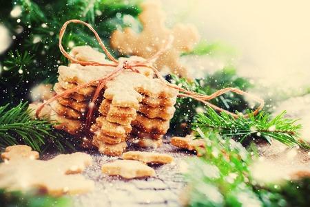 galletas de jengibre: Pila de galletas de jengibre copos de nieve atado por una cuerda en la Composición de Navidad decorado con el árbol de abeto. Ilustrado con nieve retirada. Tono cálido