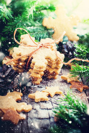 galletas de jengibre: Pila de galletas de jengibre copos de nieve atado por una cuerda en el fondo de madera. Decorado con conos de pino, árbol de abeto. Ilustrado con nieve retirada. Tono cálido
