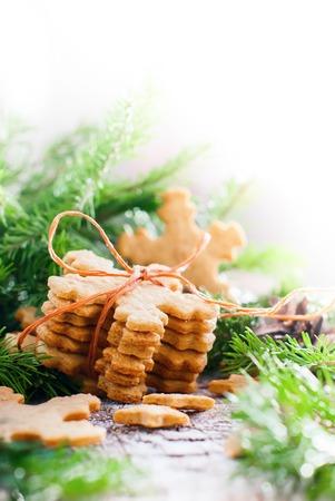 galletas de jengibre: Los copos de nieve galletas de jengibre atado por una cuerda en la Composición de Navidad decorado con el árbol de abeto en el fondo de madera. Aislado en blanco