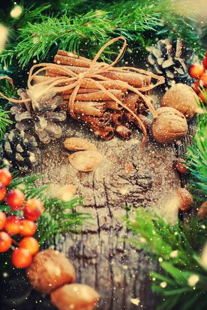 berryes: Christmas Card. Bunch with Cinnamon Sticks tied up by a Rope, Fir Tree, Natural Food on a Wooden Background. Drawn Snow. Toned