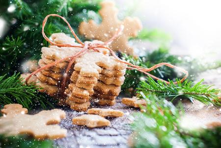galletas de jengibre: Pila de galletas de jengibre copos de nieve atado por una cuerda en la Composición de Navidad decorado con el árbol de abeto. Ilustrado con nieve retirada