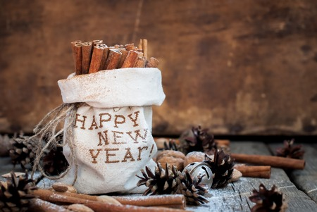 linen bag: Christmas Aroma Spices Ingredients on Wooden Background. Sticks of Cinnamon in Linen Bag Embroidered with Happy New Year, Pine cones, Walnuts