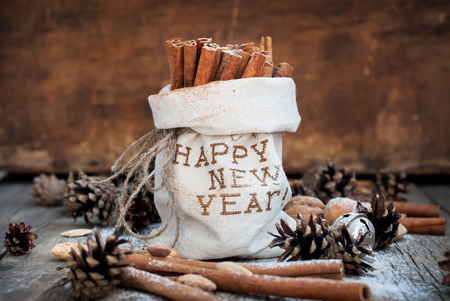 linen bag: Christmas Aroma Spices Ingredients on Wooden Background. Sticks of Cinnamon in Linen Bag Embroidered with Happy New Year, Pine cones, Walnuts. Natural Presents