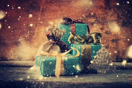 moños de navidad: Christmas Gifts and Drawn Snowfall. Festive Boxes in Blue Paper with Different Color Bows on Wooden Background. Toned