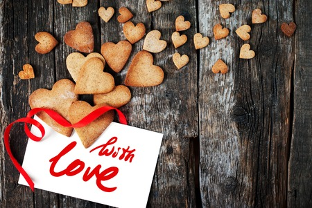 love shape: Card with Message With Love on the Letter and Gingerbread Cookies in the Shape of Heart at Valentine Day