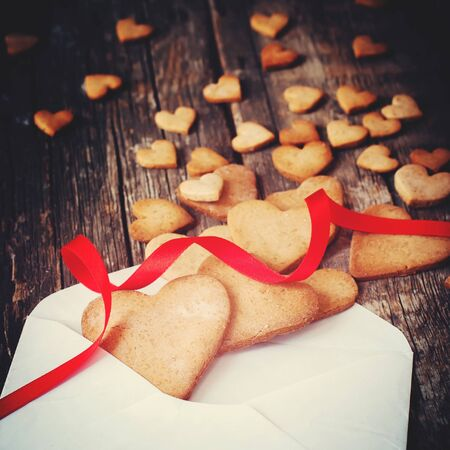 love shape: Gingerbread Cookies in the Shape of Heart from Letter with Red Ribbon on Wooden Table. Love Valentine Day concept. Toned