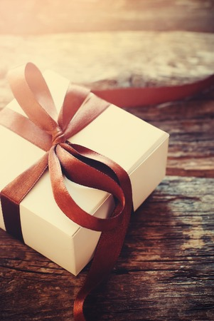 happy valentines: Gift Festive Box Brown Ribbon on Wooden Background. Light Toned Effect. Men Present