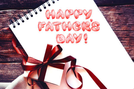 fun day: Festive White Box with Brown Bow Ribbon Album Congratulation with Fathers Day Isolated on White. Funny Text Stock Photo