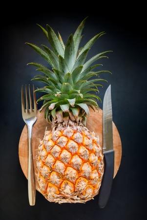 top veiw: Fruit Fresh Pineapple on Black Background Fork Knife Chopping Board Diet Concept  Top Veiw Stock Photo