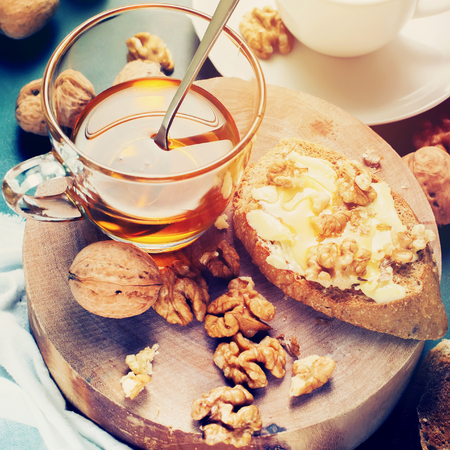 instagram: Useful Breakfast Toast with Honey Walnuts on Chopping Board to Tea Stil Life Table Healthy Food  Effect Toned Stock Photo