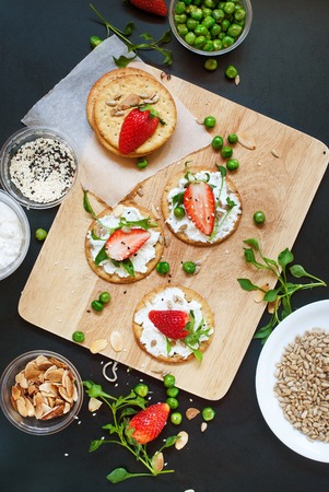 summer fruits: Healthy Appetizer Small Sandwiches Cottage Cheese Strawberry Seeds Peas Almond Flakes Sprouts Summer Fruits Vegetables on Crisp Cookies Top view