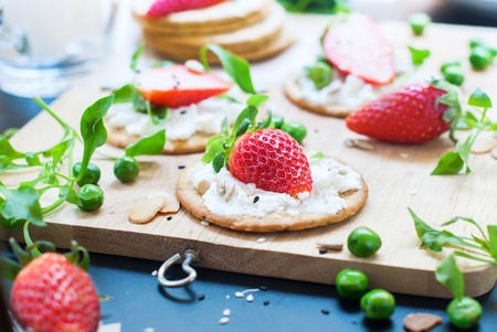 summer fruits: Fresh Summer Snack Sandwiches Cottage Cheese Strawberry Seeds Peas Almond Flakes Summer Fruits Vegetables Crackling Cookies on Chopping Board