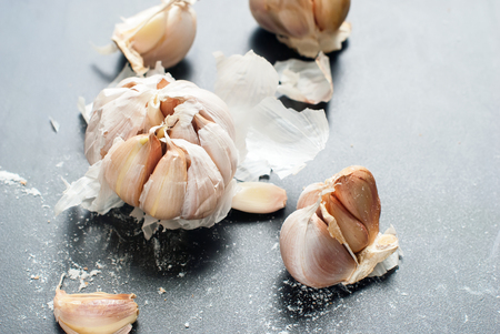 grew: Organic Garlic Clove Bulb Whole Broken on Black Table Background