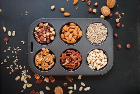 hazel nut: Assortment Nuts in Pastry Mold Peanut Almond Walnut Filbert Hazel Nut Sunflower Pecan Black Wooden Background Scattered Top view Healthy Concept Stock Photo