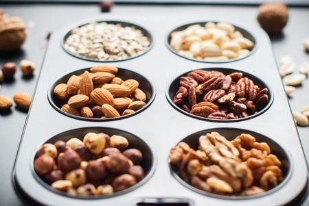 filbert nut: Assortment Nuts in Pastry Mold Peanut Almond Walnut Filbert Hazel Nut Sunflower Pecan Black Wooden Background Scattered Top view Healthy Concept Stock Photo