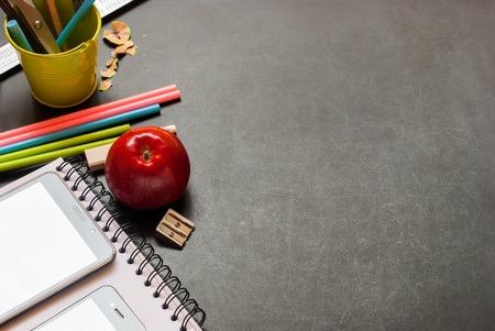 Di nuovo al concetto dei rifornimenti di scuola del fondo della lavagna del gesso del nero di progettazione dello spazio della copia della matita della matita di colore del taccuino di Apple del taccuino di Apple