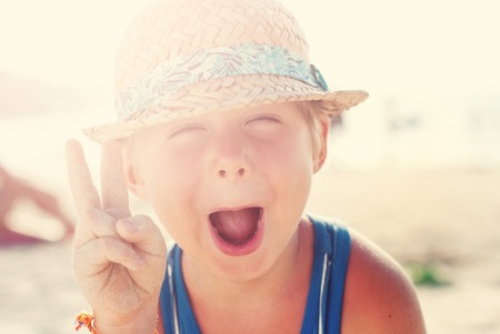 overindulgence: Funny Wriggles Boy Wattled Hat Make Fingers V Gesture Summer Beach Day Background Toned Stock Photo