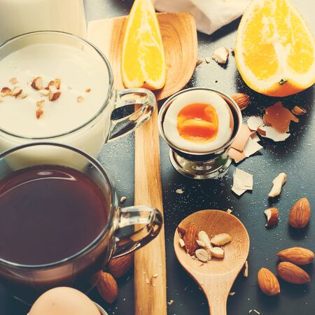 pedant: Healthy Assortment Breakfast Coffee Toast Egg Almond Yogurt Milk Porridge Orange Juice Black Table Top View
