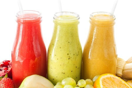 tropical drink: Row Fresh Juices Smoothie Three Bottles Red Green Orange Fruits Vitamins Healthy Concept isolated on white Stock Photo