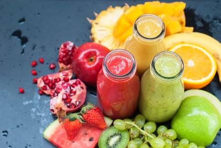 cocaine: Fresh Juices Smoothie Three Bottles Red Green Orange Tropical Fruits Water Melon Strawberry Apple Kiwi Grapes Orange Mango Banana ine Apple Pomegranate Grape Selective focus Stock Photo