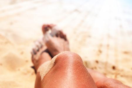 Beautiful Suntan Female Legs on Sand Beach Dark Skin Sun Rays Tropical Holiday Vacation Concept