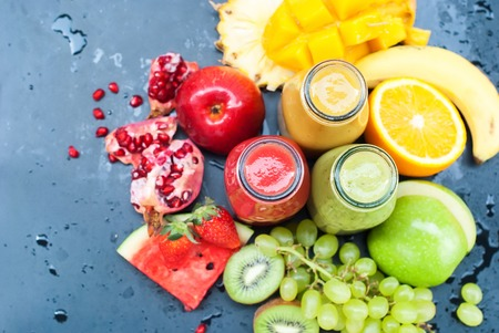 Fresh Juice Smoothie Color Tropical Fruits Strawberry Water Melon Kiwi Apple Orange Mango Banana Pine Apple Grape Pomegranate Bottles Top View Black Background Selective Focus Standard-Bild