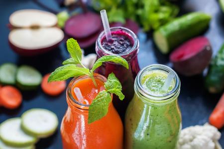 comidas saludables: Fresh Juice Smoothie Vegetables Orange Green Violet Bottles Color Black Background Selective Focus