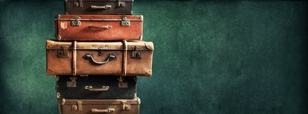 secondhand: Vintage Pile Ancient Suitcases Form of Tower Design Concept Travel Luggage Traveler on Shabby Green Background Long Format Stock Photo