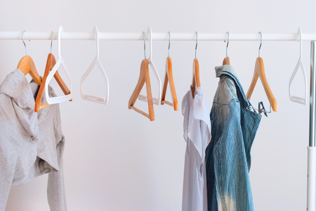 Nothing To Wear Pastel Color Female Clothes on Open Cloth Rail Wooden Hanger Grey Wall Standard-Bild