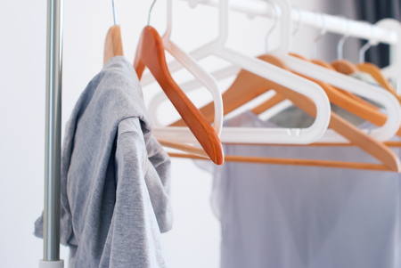 nothing: Wooden Plastic Hangers Pastel Grey Female Clothes Open Cloth Rail Gray Wall Nothing To Wear Concept Stock Photo