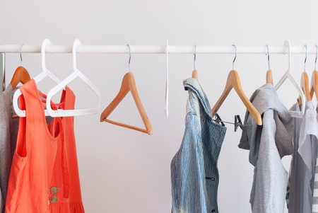 Pastel Color Female Clothes on Open Cloth Rail Wooden Hanger Grey Wall