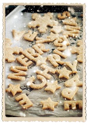 galletas de jengibre: Marco de galletas de jengibre pequeñas letras Feliz Navidad en la bandeja para hornear Dibujo nieve retro aislada en blanco Foto de archivo