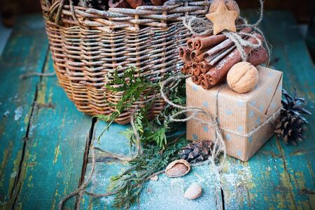 Cristmas: Christmas Ingredients on Wooden Table Boxes Stick of Cinnamon Linen Cord Pine cones Cookies Walnuts Stock Photo