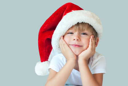 isolated on grey: Funny Boy in Christmas Santa Hat with Smile on Face Christmas theme Isolated Grey