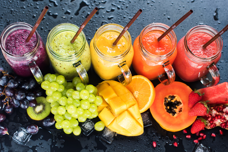 multy: Fresh Color Juices Smoothie Violet Green Yellow Orange Red from Tropical Fruits Kiwi Water Melon Strawberry Apple Orange Banana Pine Apple Mango Pomegranate Grape Bottles Rainbow Dark Background Stock Photo