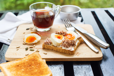 pedant: Healthy Breakfast Coffee with Toast Tuna Eggs Sunflower Seeds Toasted Bread Fork Knife Top View Black Background