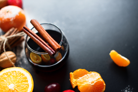 Mulled Wine Hot Drink with Spices Citrus Fruits Oranges Tangerines Apples Black Background Christmas Beverage Copy Space Stock Photo