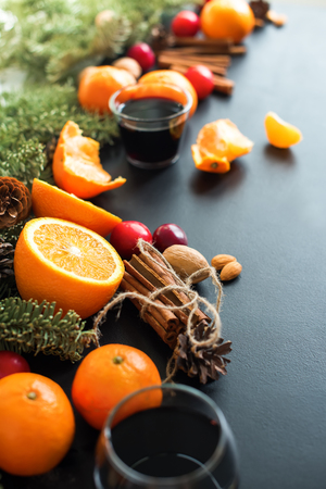 Mulled Wine Hot Drink with Spices Citrus Fruits Oranges Tangerines Apples Plums Black Background Christmas Beverage Copy Space Stock Photo