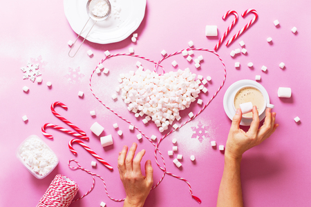 Concept Preperation Christmas Holiday Heart Marshmallows Candy Cane Cocoa with Female Hands Pink Background Copy Space Flat Lay Top View Winter Traditional Food