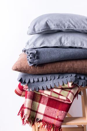tejido de lana: stacked colorful pillows cushion plaid linen textile wooden chair near white wall pile concept