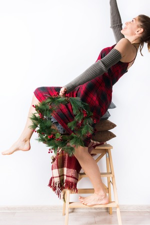 preparation to Merry Christmas one woman red tartan dress decorate house with wreath new year concept