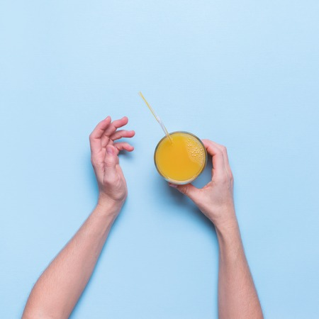 Female Hands Holds Fresh Juice Fruit Orange Glass Color Blue Background Top View Flat Lay Standard-Bild