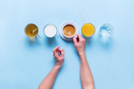여성 손 보유 그룹 유용한 다채로운 음료 커피 우유 차 오렌지 주스 물 평면 누워 아직도 테이블 상위 뷰 파란색 배경 스톡 콘텐츠
