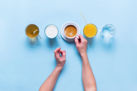 Female Hands Holds Group Useful Colorful Beverages Drink Coffee Milk Tea Orange Juice Water Flat Lay Still Life Table Top View Blue Background Foto de archivo