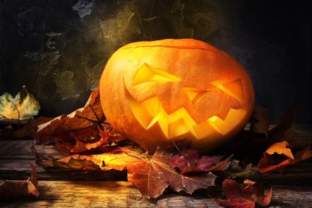 Burning Halloween pumpkin lantern head jack with leaves on wooden background