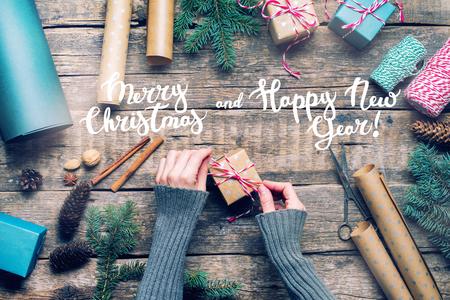 Weibliche Hände, die Weihnachtsgeschenke im Weinlese-beige blauen Papier und im natürlichen Dekor verpacken. Tannenzweigkegel-Zimt auf hölzerner Retro- Tischplatten-Ansicht-Ebenenlage Standard-Bild - 89284755