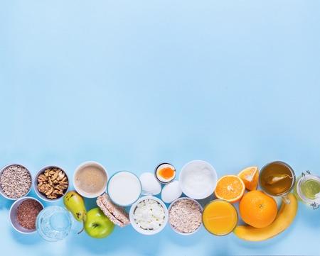 Nützlicher bunter Frühstücks-Kaffee-Milch-Tee trägt Hüttenkäse-Hafer-Ebenen-Lage-Stillleben-Tischplattenansicht-Blau-Hintergrund Früchte Standard-Bild